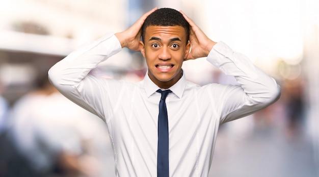 O homem de negócios afro americano novo toma as mãos na cabeça porque tem a enxaqueca na cidade