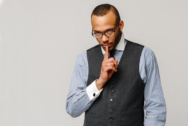 O homem de negócios afro-americano que mostra quieto assina sobre a parede cinzenta clara.