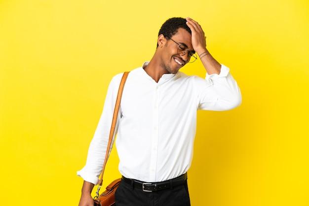 O homem de negócios afro-americano sobre fundo amarelo isolado percebeu algo e tem a intenção de encontrar a solução