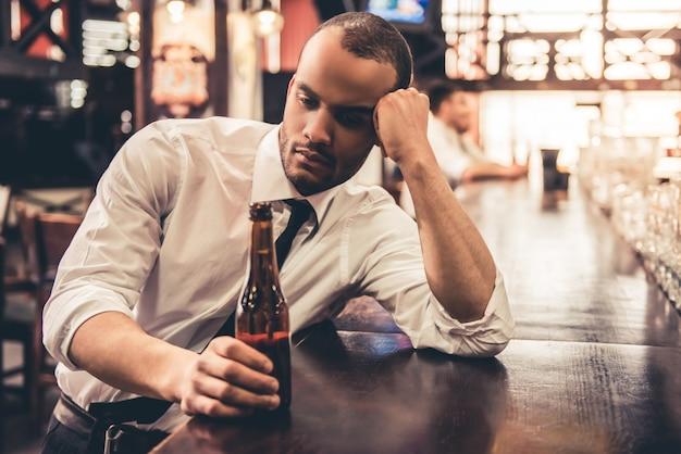 O homem de negócios afro-americano triste considerável está bebendo a cerveja.