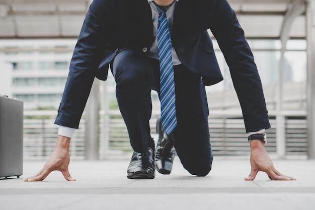 O homem de negócios ajustado na posição de corrida do começo prepara-se para lutar na raça do negócio.