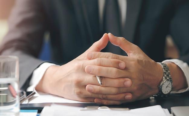 O homem de negócios apertou as mãos apertadas junto ao sentar-se na mesa de escritório.