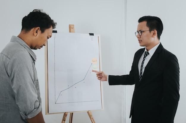 O homem de negócios asiático que sente seja sério quando seu chefe se queixar sobre o trabalho.
