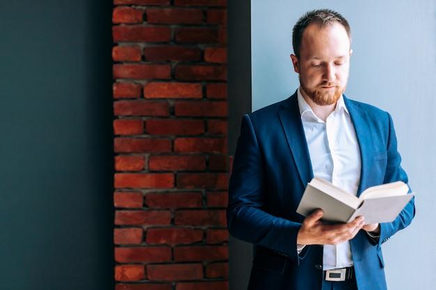 O homem de negócios bem sucedido em um terno senta-se, está e lê-se um livro no escritório.