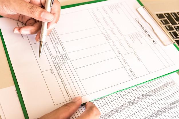 O homem de negócios calcula contas no local de trabalho com papel.