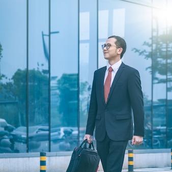 O homem de negócios carregava seu laptop em frente ao prédio de escritórios