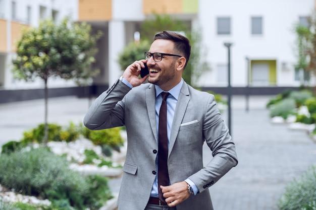 O homem de negócios caucasiano de sorriso vestiu-se no vestuário formal e com monóculos que fala no telefone esperto. exterior do centro de negócios.