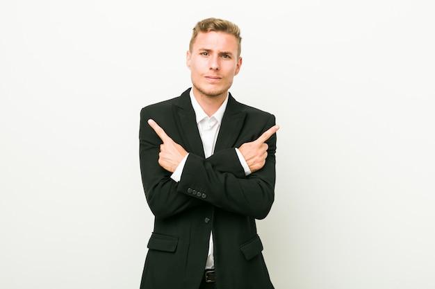 O homem de negócios caucasiano jovem aponta lateralmente, está tentando escolher entre duas opções.