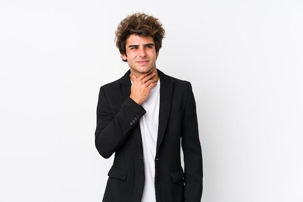 O homem de negócios caucasiano jovem contra uma parede branca isolada sofre dor na garganta devido a um vírus ou infecção.
