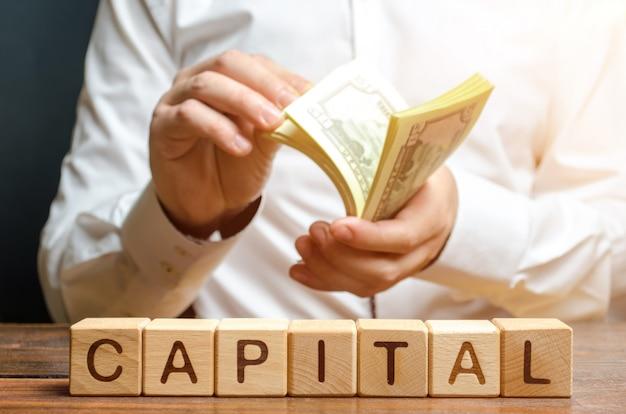 O homem de negócios conta o dinheiro no do capital do subtítulo. capitalismo