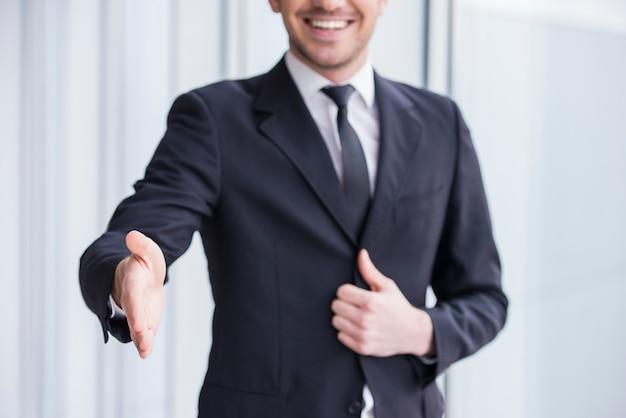 O homem de negócios de sorriso está vestindo no terno, aperto de mão a você.