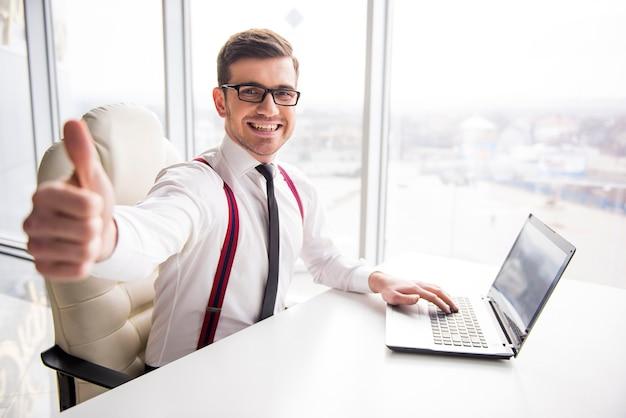 O homem de negócios de sorriso novo está mostrando o polegar acima.