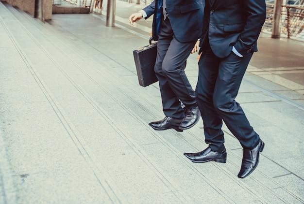 O homem de negócios defocused ou blured que anda as escadas com fundo da cidade, homens de negócios vai ao conceito do sucesso, estilo do vintage.