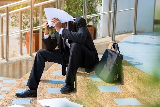 O homem de negócios desempregado dos povos asiáticos sublinha sentado na escada, conceito de falha de negócios e problema de desemprego devido ao impacto global do covid-19.