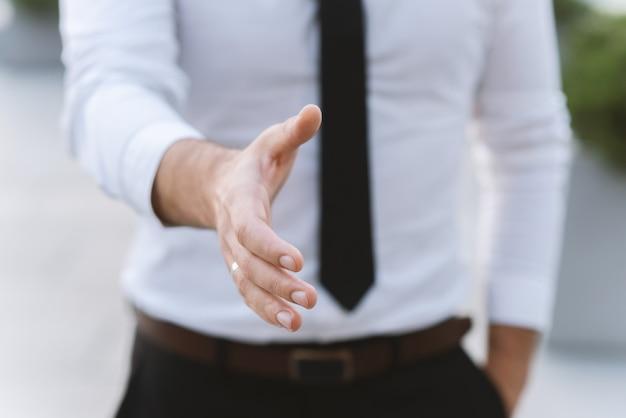 O homem de negócios do homem em uma camisa e em uma gravata brancas dá uma mão para um cumprimento.