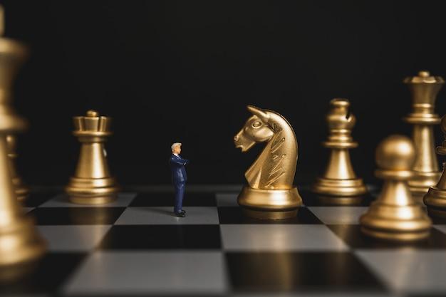 O homem de negócios do líder está na frente da xadrez do cavalo com confiança.