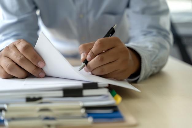 O homem de negócios documenta papéis do relatório comercial, succes do trabalho analisa planos do original