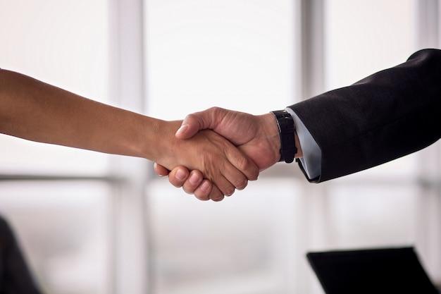 O homem de negócios e a mulher de negócios agitam as mãos no acordo.