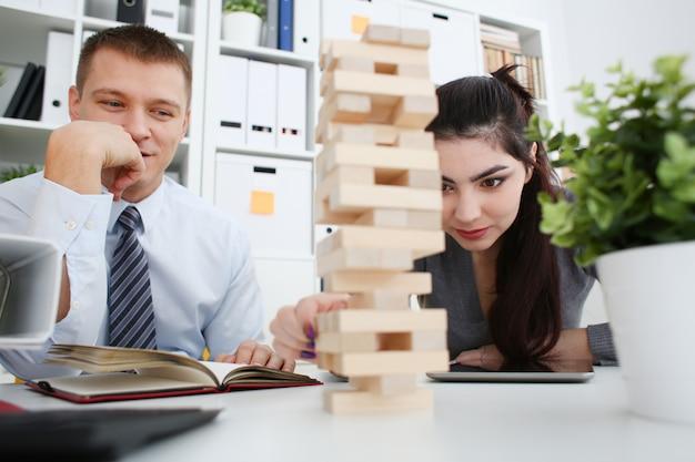 O homem de negócios e a mulher de negócios jogam na mão da estratégia que rearranja os blocos de madeira envolvidos durante a ruptura no trabalho no conceito de assento de assento do passatempo da alegria do divertimento da pilha do jogo da tabela do escritório.