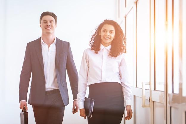 O homem de negócios e uma mulher caminhando no corredor do escritório