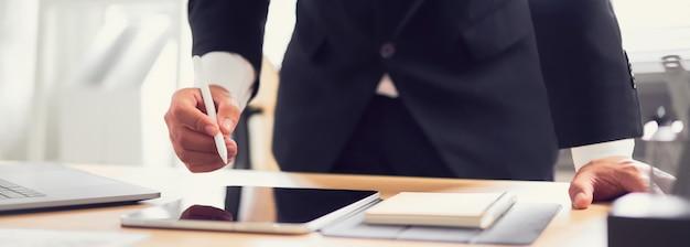 O homem de negócios entrega guardar a pena digital e usar a tabuleta com o computador no escritório.