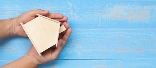 O homem de negócios entrega guardar o modelo de madeira da casa na tabela de madeira azul.