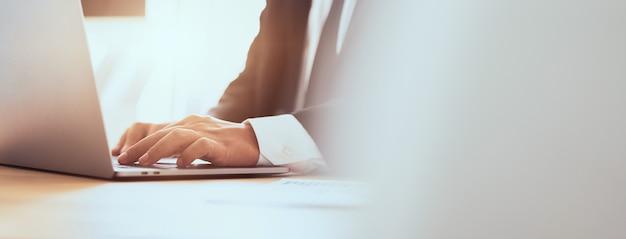 O homem de negócios entrega usando o laptop com o teclado da imprensa no escritório. proporção do banner para anúncios.