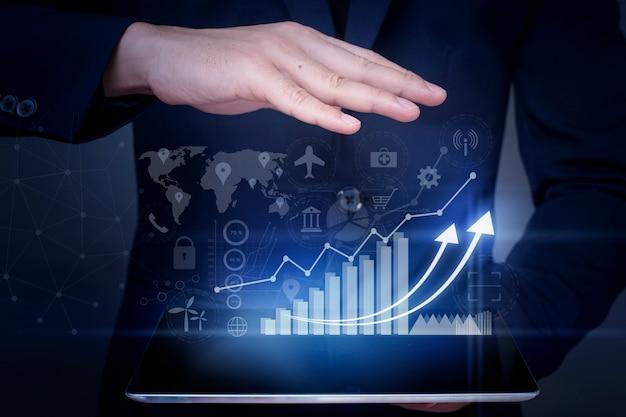 O homem de negócios está guardando o gráfico do crescimento financeiro e analisando dados comerciais, plano de negócios e conceito da estratégia.