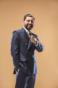 O homem de negócios feliz aponta e quer você, retrato de meio comprimento closeup