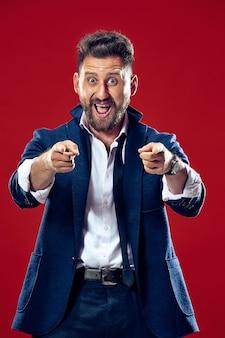 O homem de negócios feliz aponta para você e quer seu retrato na parede vermelha