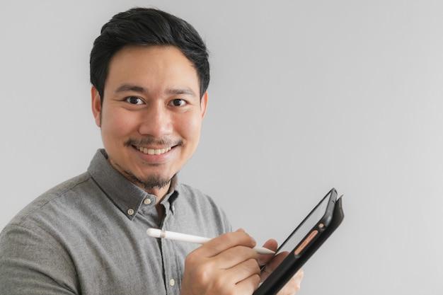 O homem de negócios feliz e do sorriso do empresário trabalha em sua tabuleta com fundo cinzento.