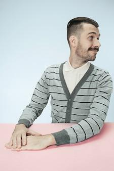 O homem de negócios feliz e sorridente, sentado à mesa no fundo azul do estúdio. o retrato em estilo minimalista