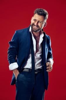 O homem de negócios feliz em pé e sorrindo contra a parede vermelha.