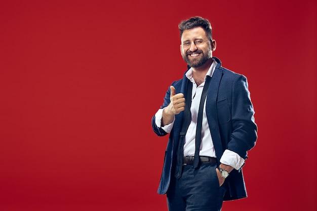 O homem de negócios feliz em pé e sorrindo contra a parede vermelha