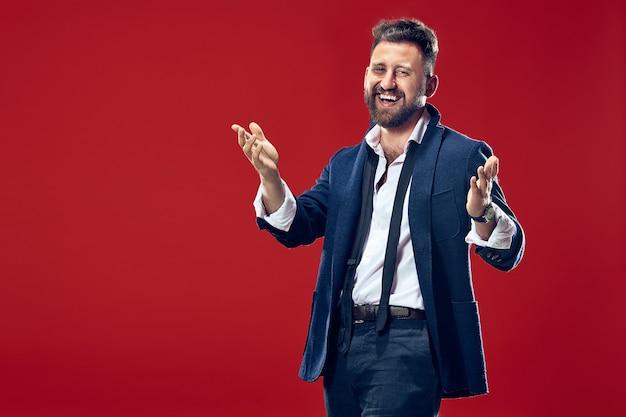 O homem de negócios feliz em pé e sorrindo contra o vermelho.