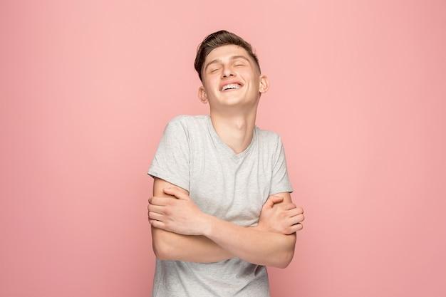 O homem de negócios feliz que está e que sorri contra o espaço cor-de-rosa.