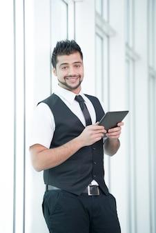 O homem de negócios indiano novo está guardando uma tabuleta nas mãos.