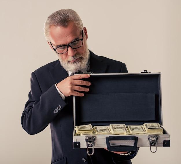 O homem de negócios maduro considerável abre o caso do dinheiro.