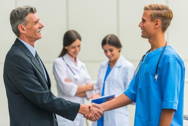O homem de negócios masculino superior agita doutores das mãos no hospital.