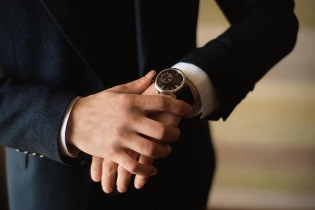 O homem de negócios masculino veste e ajusta seu relógio, preparando-se para uma reunião. relógio
