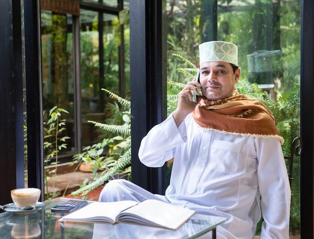 O homem de negócios muçulmano envelhecido meados de asiático senta-se no café da bebida da cafetaria com telefone móvel esperto na tabela.