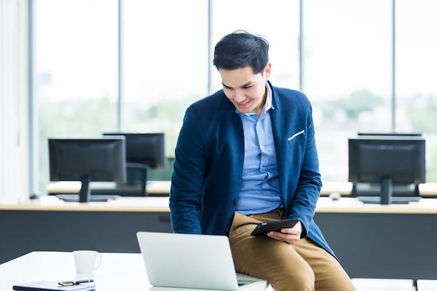 O homem de negócios novo asiático do humor feliz que trabalha com laptop senta-se em cima da mesa na sala do escritório.