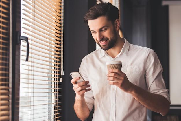 O homem de negócios novo considerável está usando um smartphone.