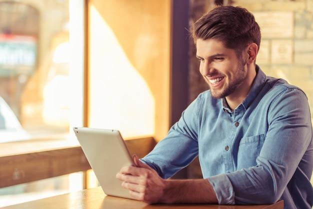 O homem de negócios novo considerável está usando uma tabuleta.