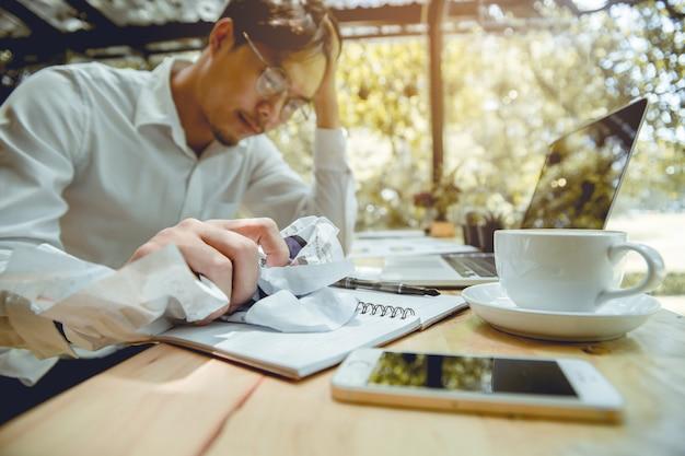 O homem de negócios novo esmagou o papel com esforço.