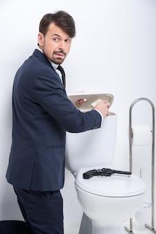 O homem de negócios novo está escondendo o dinheiro no tanque do toalete.