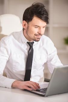 O homem de negócios novo está olhando o portátil em seu escritório.