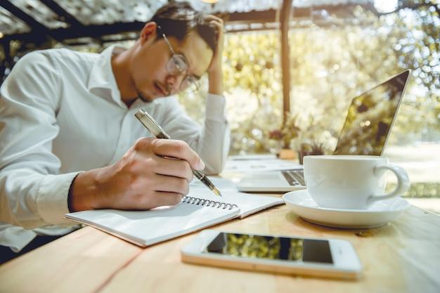 O homem de negócios novo seja escreve o caderno com esforço.