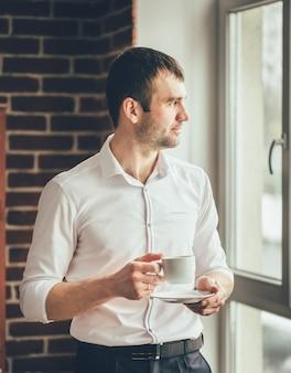 O homem de negócios olha em uma janela com uma xícara de café em sua mão do escritório. t