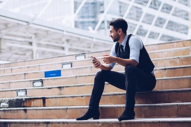 O homem de negócios olhou para o rosto com uma ligeira barba, as mãos segurando um smartphone,